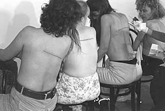 "photo-document of ""160 CM LINE TATTOOED ON 4 PEOPLE,"" El Gallo Arte Contemporáneo. Salamanca, Spain. December 2000"