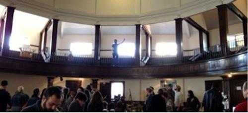 Chris Fritton, balcony, directs the Buffalo Small Press Book Fair.