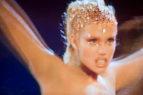 "Stripper Nomi Malone (Elizabeth Berkley) rapaciously hogs the star spot.  Photograph by Frank Mullaney: ""Head Dress"" (2009)."